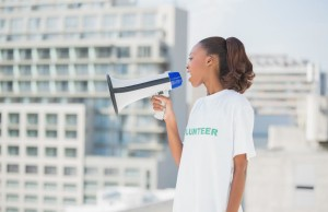 Cute volunteer woman shouting in megaphone outdoors on urban background