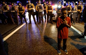 Amarion Allen, 11-years-old, stands in front of a police line shortly before shots were fired in a police-officer involved shooting in Ferguson, Missouri August 9, 2015. Two people were shot in the midst of a late-night confrontation between riot police and protesters, after a day of peaceful events commemorating the fatal shooting of Michael Brown by a white officer one year ago.  REUTERS/Rick Wilking      TPX IMAGES OF THE DAY      - RTX1NPTC